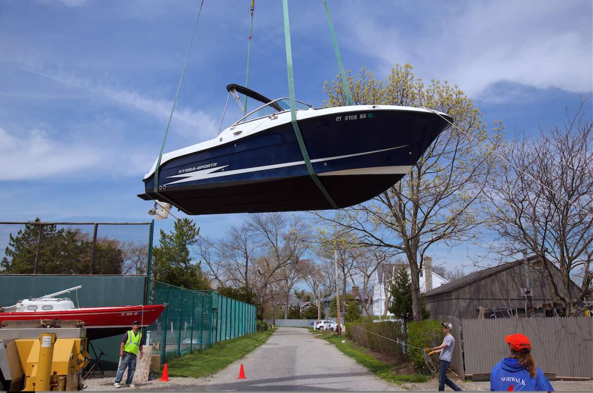 The crane carries a boat across Baywater Drive toward the water. - All photos Jarret Liotta