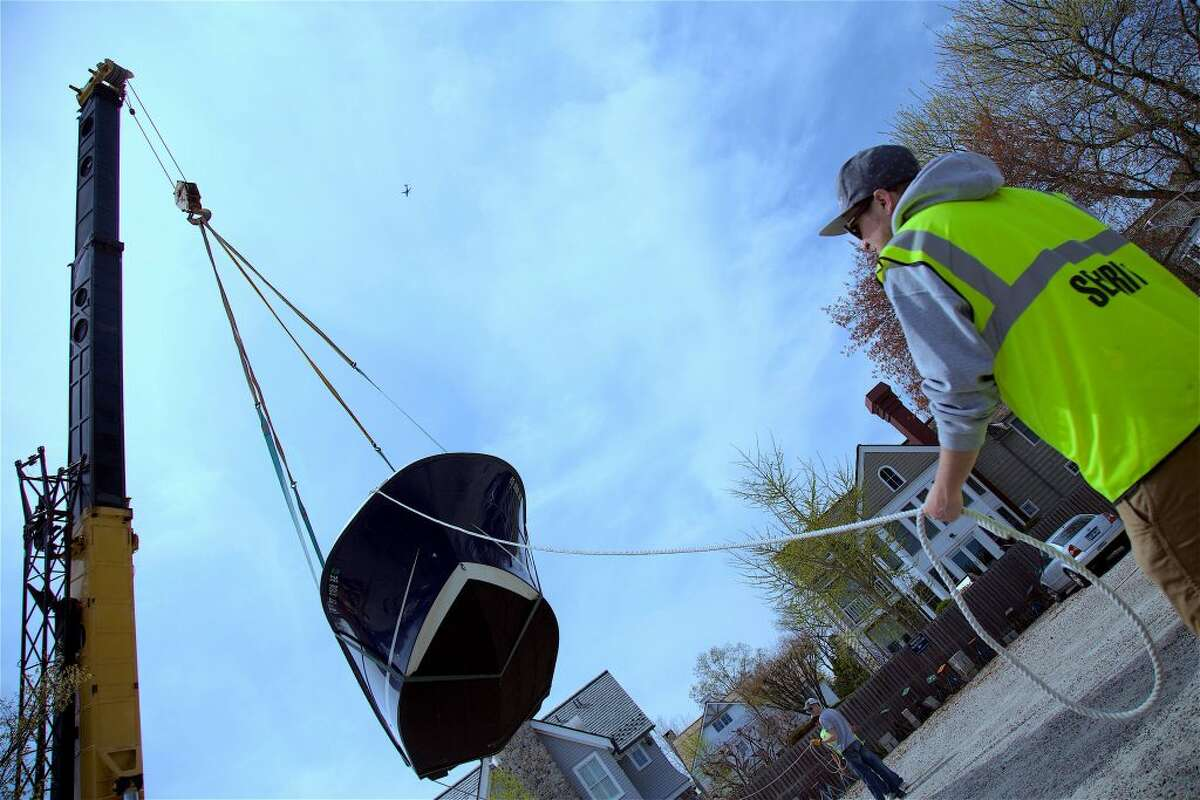 Jon Leventhal, of the Noroton Yacht Club's launch staff, helps guide the boat through the air.