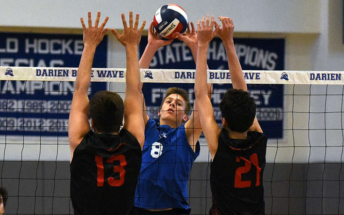 Darien's Tyler Herget soars at the net as a pair of New Canaan Rams defend during the FCIAC boys volleyball playdowns at DHS last spring. - Dave Stewart photo