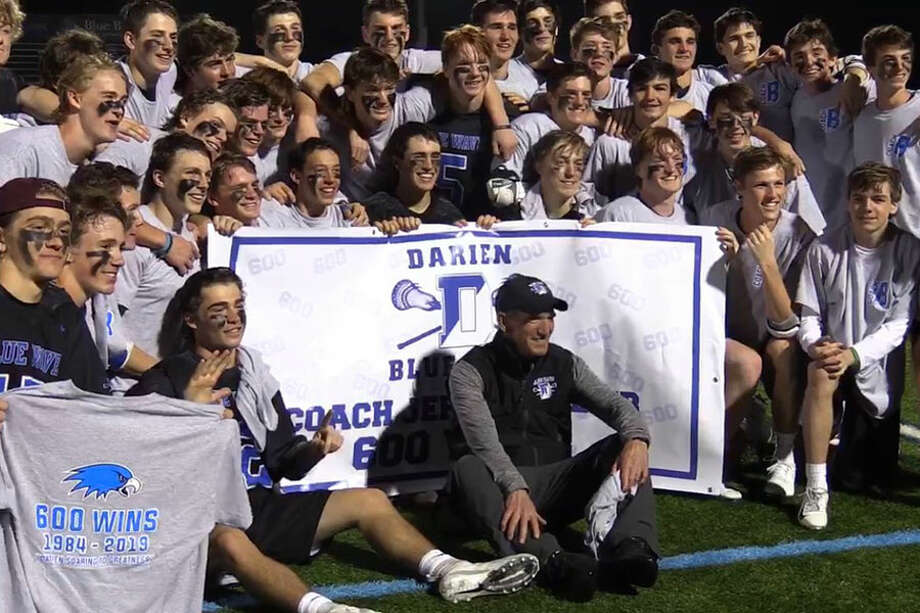 Darien coach Jeff Brameier (center) poses with the rest of the Darien boys lacrosse players after they defeated Wilton 18-6 for Brameier's 600th career victory as head coach. — Sean Patrick Bowley/Hearst Connecticut Media