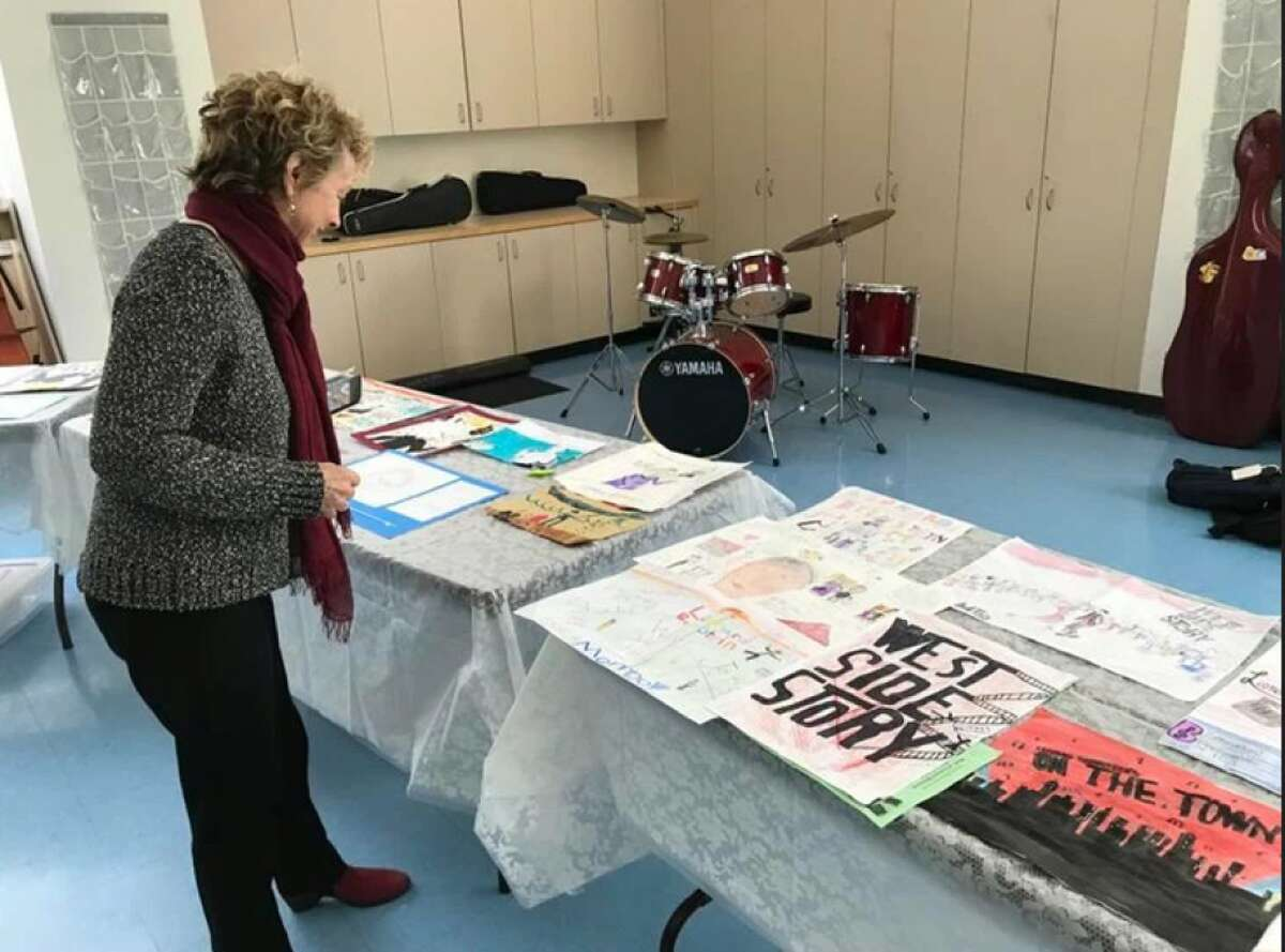 Jamie Bernstein enjoying the Leonard Bernstein Poster Contest submissions from our elementary and middle schools.