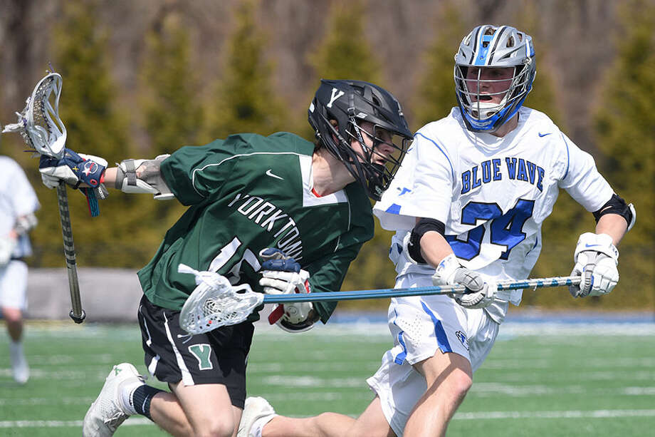 Darien's Tyler Strub (34) defends against Yorktown's Tim O'Callaghan (15) during the Wave's 11-7 win at Darien High School on Saturday, March 30. — Dave Stewart/Hearest Connecticut Media / Hearst Connecticut Media