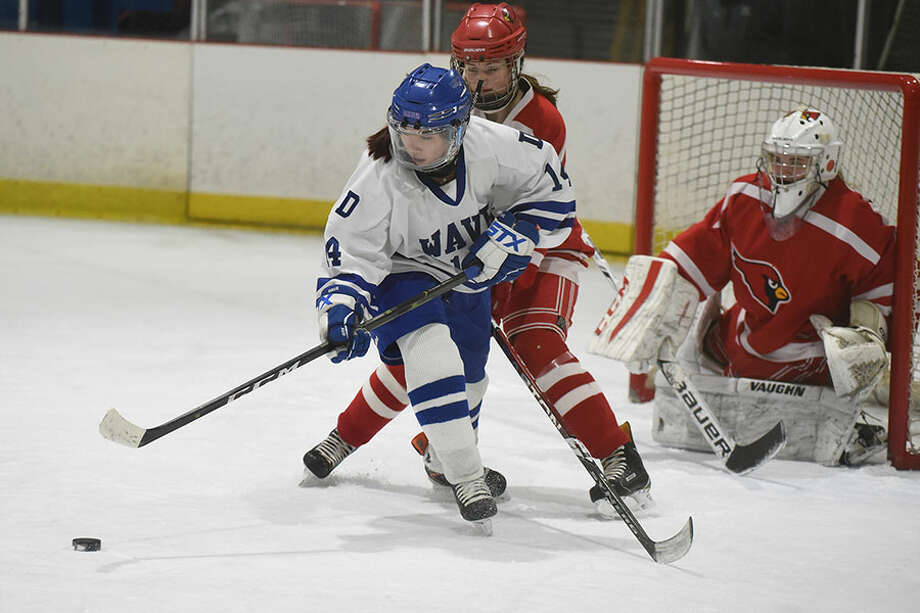 Darien's Caitlin Chan (14) gets to the puck in front of the Greenwich goal during the girls hockey state quarterfinals at the Darien Ice House on Saturday, March 2. — Dave Stewart/Hearst Connecticut Media / Hearst Connecticut Media