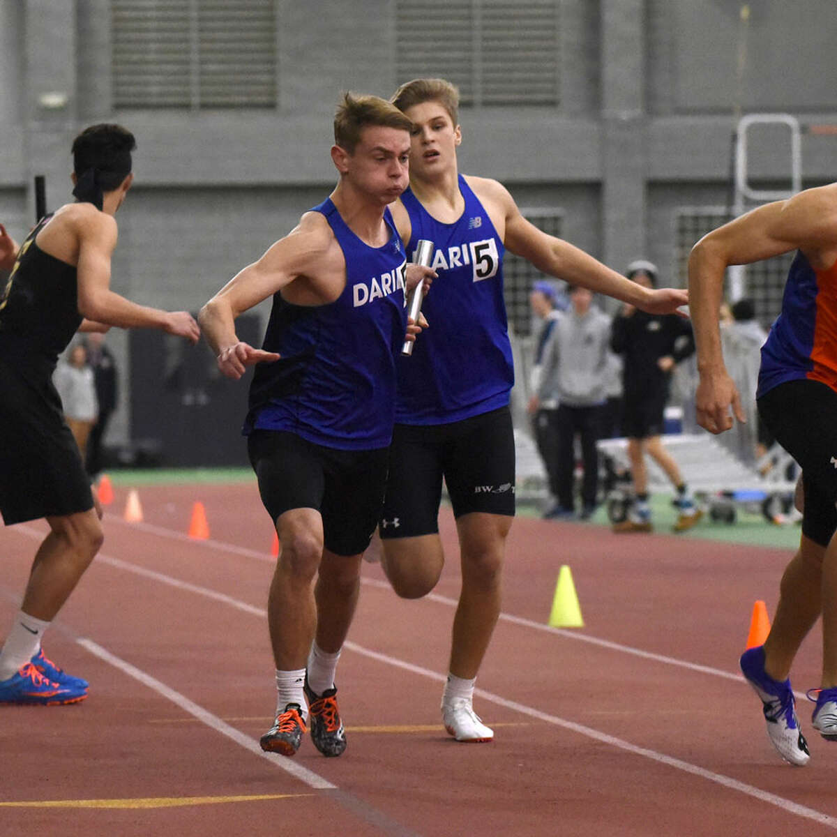 Darien's Jack Holly takes the baton from teammate Austin Dehmel during the 4x400 relay at the FCIAC indoor track and field championships in New Haven on Thursday, Jan. 31. - Dave Stewart/Hearst Connecticut Media photo