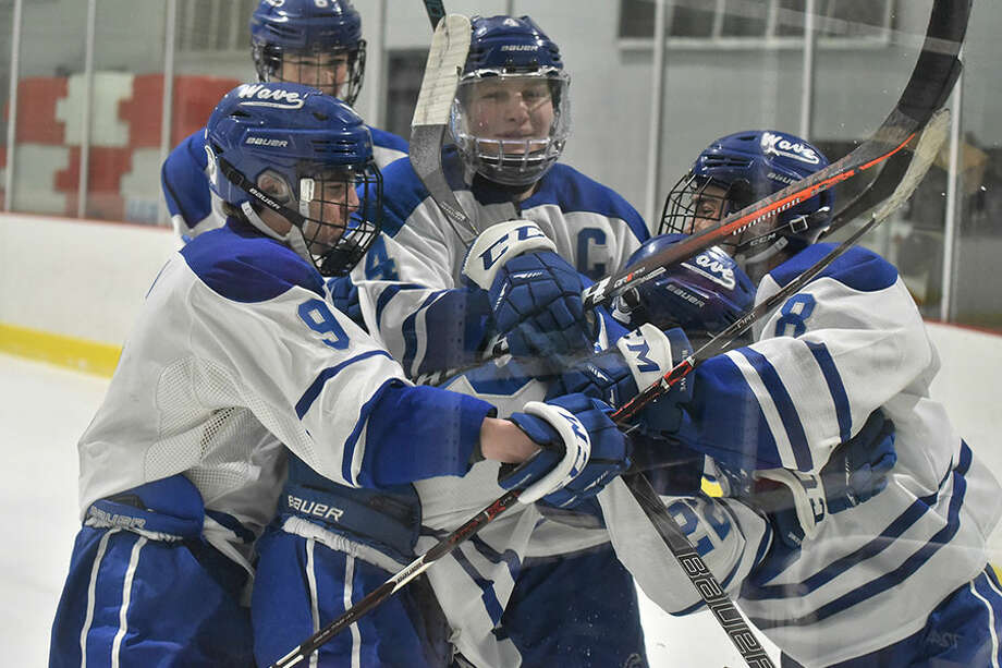 Darien players mob teammate Bennett McDermott after he scored the first goal against rival New Canaan in a boys ice hockey game played at the Darien Ice House on Wednesday, Jan. 30. — Dave Stewart/Hearst Connecticut Media photo