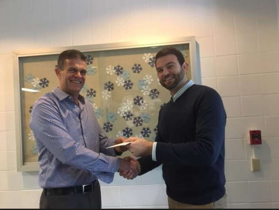 Geoff Garfield handed a check to Ox Ridge principal Dr. Luke Forshaw receiving check for the school's effort in helping sell tickets.