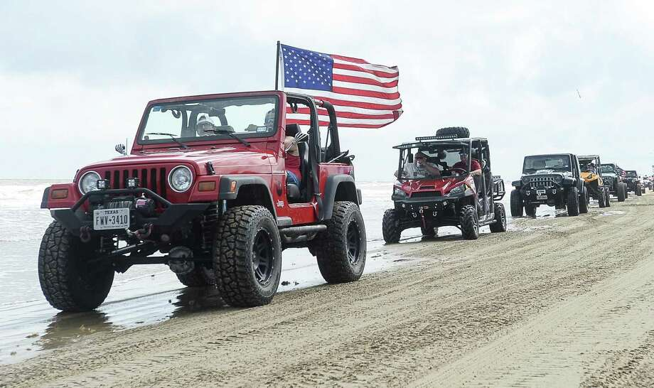 A Jeep with an American flag drives down Crystal Beach during the annual Go Topless Jeep weekend in Crystal Beach on Friday. Photo taken on Friday, 05/17/19. Ryan Welch/The Enterprise Photo: Ryan Welch / Ryan Welch / The Enterprise / © 2019 Beaumont Enterprise