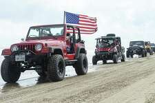 A Jeep with an American flag drives down Crystal Beach during the annual Go Topless Jeep weekend in Crystal Beach on Friday. Photo taken on Friday, 05/17/19. Ryan Welch/The Enterprise