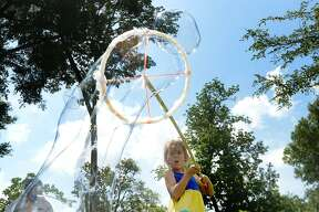 Hayden Lindsay joins in the outdoor bubble-making stations during the Bubble Day event at Rogers Park. Texas Energy Museum partners with the Beaumont Public Library for the summer series, which combines the fun of bubble-making with science. Wednesday, July 11, 2018 Kim Brent/The Enterprise