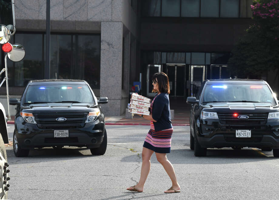 Kim Duchamp carries doughnuts to people in the Jefferson County parking lot during a bomb threat on Thursday. In a second threat this week, employees and visitors of the the Jefferson County Courthouse were evacuated from the building Thursday morning after a bomb threat was made. The first threat was called in Wednesday afternoon.  Photo taken Thursday, 6/20/19 Photo: Guiseppe Barranco/The Enterprise / Guiseppe Barranco ?