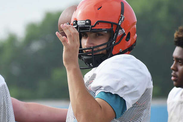 Edwardsville quarterback Luke Oglebsy warms up on the sideline before a 7-on-7 drill during a workout Tuesday inside the District 7 Sports Complex.