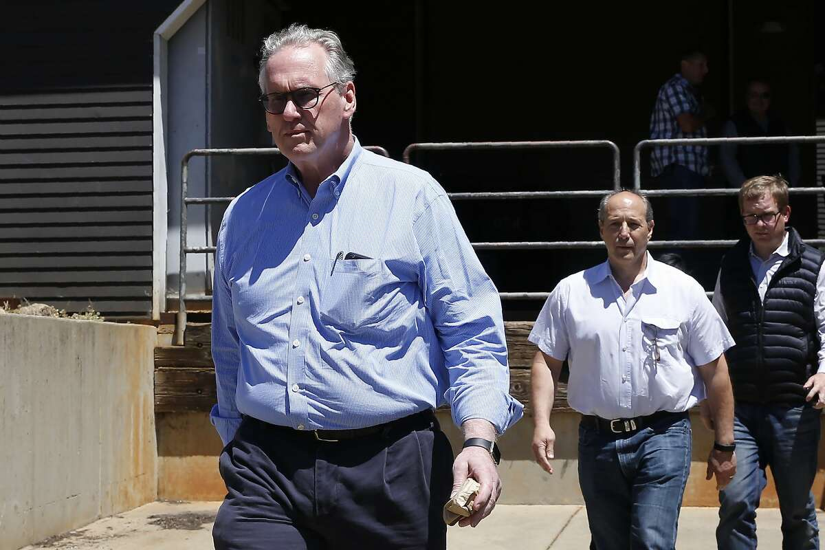 William Johnson, left, the chief executive officer for Pacific Gas & Electric Co., leaves the Paradise Performing Arts Center during a tour of fire ravaged Paradise, Calif., Friday, June 7, 2019. Johnson, the PG&E board and others leaders were ordered by United States District Judge William Alsup to tour the destruction caused last November's Camp Fire. (AP Photo/Rich Pedroncelli)