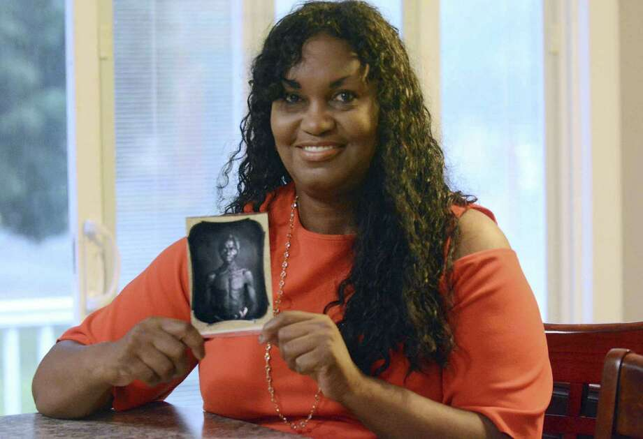 In this July 17, 2018, photo, Tamara Lanier holds an 1850 photograph of Renty, a South Carolina slave who Lanier said is her family's patriarch, at her home in Norwich, Conn. The portrait was commissioned by Harvard biologist Louis Agassiz, whose ideas were used to support the enslavement of Africans in the United States. Lanier filed a lawsuit on Wednesday, March 20, 2019 in Massachusetts state court, demanding that Harvard turn over the photo and pay damages. (John Shishmanian/The Norwich Bulletin via AP) Photo: John Shishmanian /The Norwich Bulletin Via AP / The Norwich Bulletin