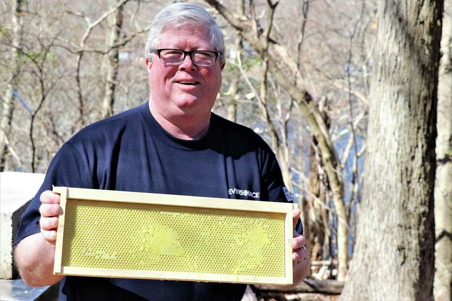 East Haddam resident Pat Capel, a supervisor in Eversource's natural gas meter services department in Meriden, collects honey from thousands of bees on his and his neighbor's properties. Photo: Contributed Photo