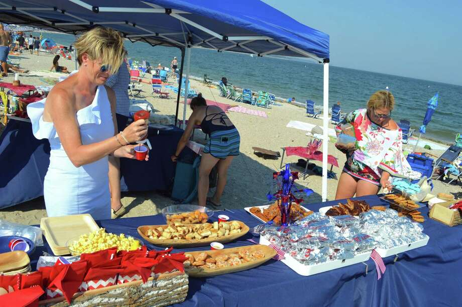 Preparing a spread worth celebrating are Michelle Hogue, left, and Lauren Bromberg, both of Westport, at the Westport Fireworks at Compo Beach. Taken Monday, July 2, 2018, in Westport, Conn. Photo: Jarret Liotta / For Hearst Connecticut Media / Westport News Freelance