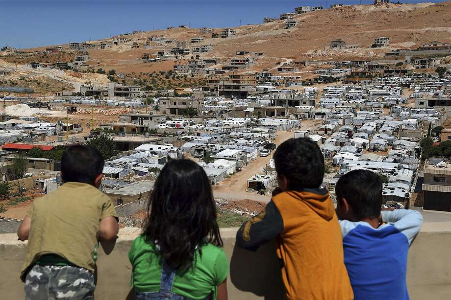 Children look from their home at a camp for Syrian refugees in the eastern Lebanese border town of Arsal. Authorities are waging their most aggressive campaign yet against refugees. Photo: Bilal Hussein / Associated Press