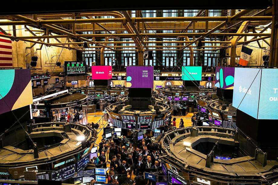Signs for Slack are highly visible on its first day of trading on the New York Stock Exchange. Photo: Brittainy Newman / New York Times