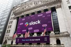 Signs for Slack at the New York Stock Exchange on the day of the workplace collaboration company's initial public offering, in Manhattan, June 20, 2019. Slack shares soared on Thursday in early trading, a sign that Wall Street remains tantalized by fast-growing young technology firms even after the recent lackluster public offerings of companies like Uber. (Brittainy Newman/The New York Times)