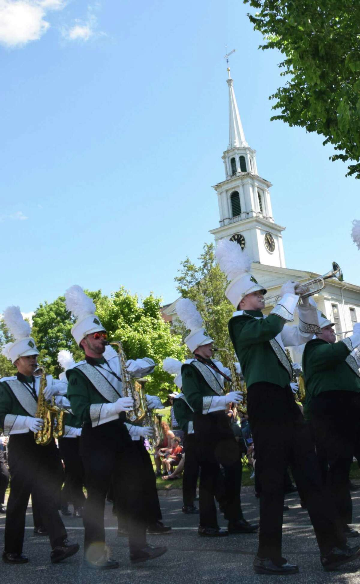 Spectrum/New Milford recognized Memorial Day with a ceremony in front of the New Milford Public Library, followed by a parade downtown. May 27, 2019. Above, members of the New Milford High School band march along Main Street, with the First Congregational Church in the background.