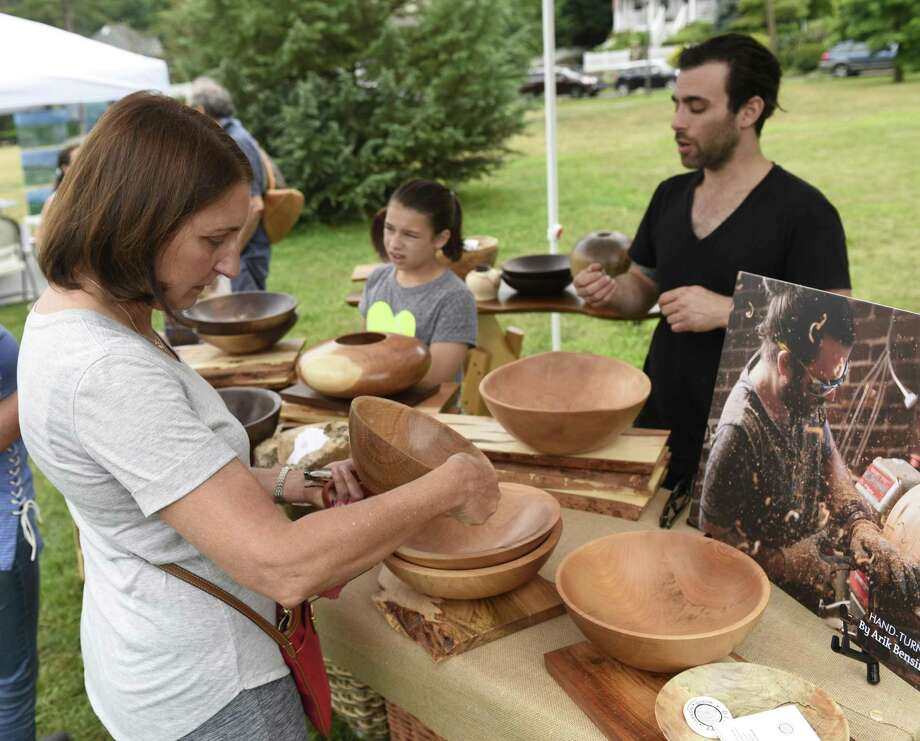 Folks admire the woodworking of local artist Arik Bensimon at the inaugural Old Greenwich Merchants Art in the Park event at Binney Park in Old Greenwich last year. The event, featuring more than two-dozen local artists exhibiting and selling their work in a variety of mediums, including painting, photography, digital art, ceramics and more, returns to the park June 23. Photo: Hearst Connecticut Media File Photo / Greenwich Time