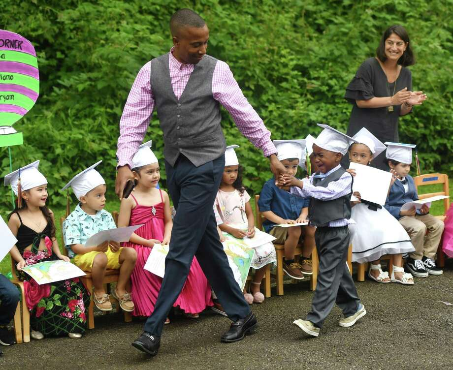 Graduating pre-K student Kyle Johnson receives a helping hand from his father, Loushen Johnson, while walking to accept his diploma on stage at the Family Centers Head Start preschool graduation ceremony at Armstrong Court in the Chickahominy section of Greenwich, Conn. Thursday, June 20, 2019. Photo: Tyler Sizemore / Hearst Connecticut Media / Greenwich Time