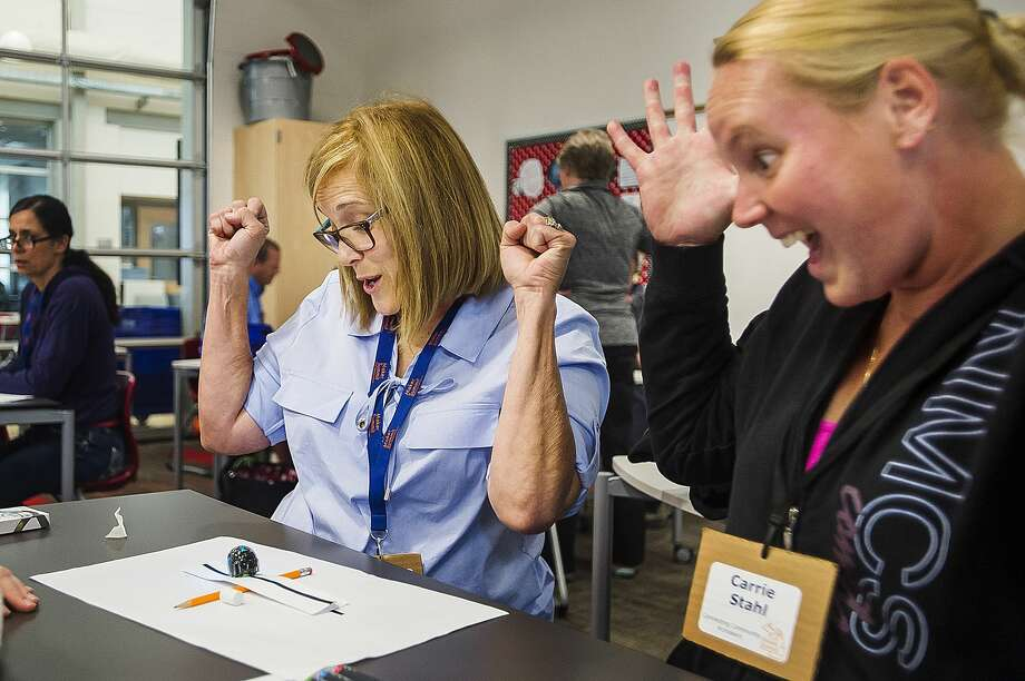 Beth Rittenberg of Vassar, left, and Carrie Stahl of McBain, right, react after getting a small programmable robot, called an Ozobot, to cross a bridge made of paper during a professional development day for educators hosted by the Regional Educational Media Center Association of Michigan on Thursday, June 20, 2019 at Central Park Elementary. (Katy Kildee/kkildee@mdn.net) Photo: (Katy Kildee/kkildee@mdn.net)