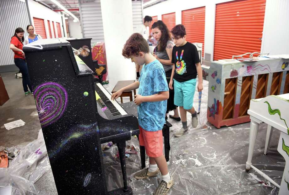 Elijah Cross, center, 10, of New Haven tries out a piano donated by Karen and Peter Murray and painted by Kelly Triolo during the International Festival of Arts & Ideas event, Free Keys CT Piano Trail, at the C. Cowles & Co. Warehouse in New Haven Thursday. Donated pianos were painted by artists during a three-day period and will be placed in public spaces for Make Music New Haven Day, a one-day festival of free concerts throughout the city on Friday, June 21. Five pianos are going to locations in New Haven. Six more are going to other area towns in Southern Connecticut. The piano being played is destined for Broadway in New Haven. Elijah and his brother, Isiah, came to the event to try out the pianos. Photo: Arnold Gold / Hearst Connecticut Media / New Haven Register