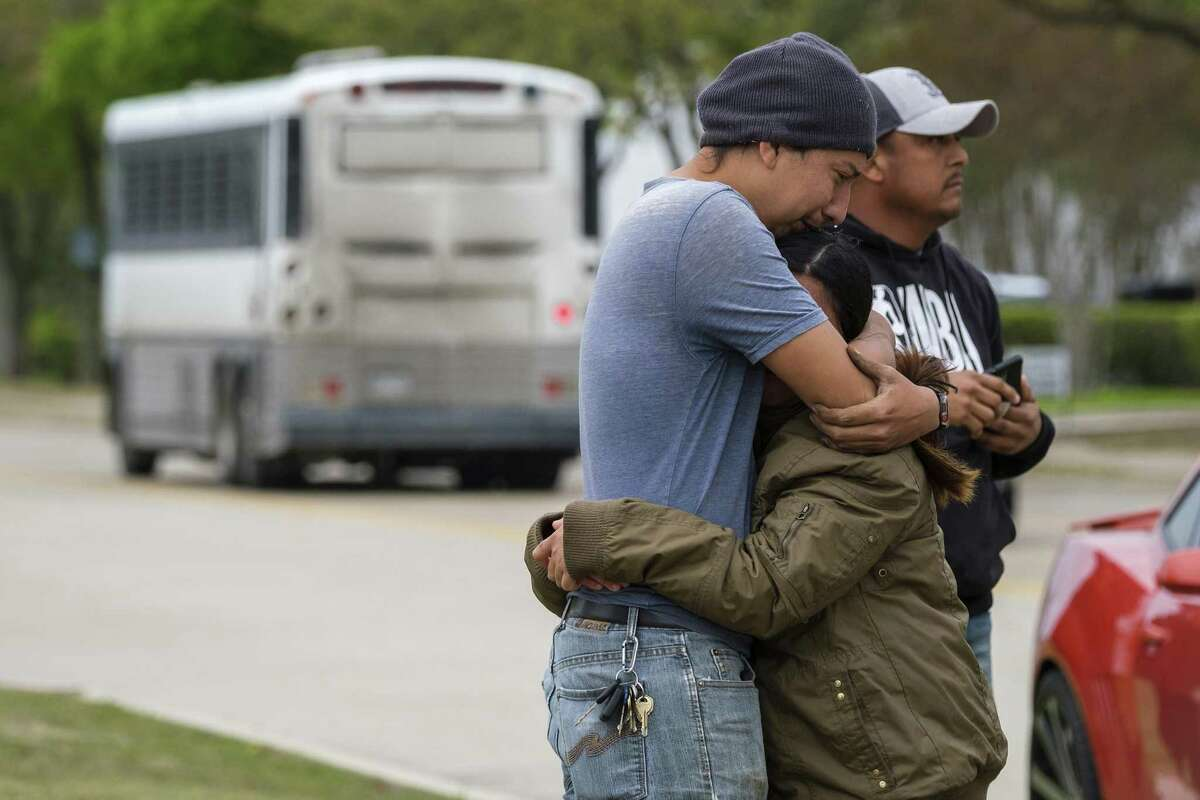 In this Wednesday, April 3, 2019 photo, a couple who did not want to give their names embrace outside CVE Group as a bus from LaSalle Corrections Transport departs the facility in Allen, Texas. U.S. Immigration and Customs Enforcement officials were detaining people at an Allen technology business Wednesday. The operation began Wednesday morning at CVE Group, a New Jersey-based company that refurbishes cellphones and other technology, on Enterprise Drive near East Bethany Drive and U.S. Highway 75. (Smiley N. Pool/The Dallas Morning News via AP)