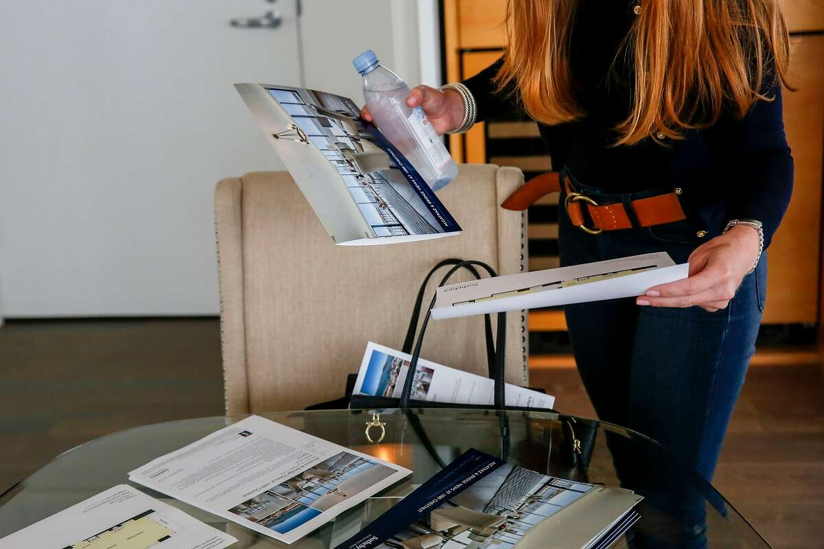 Whitney Hudak looks over literature with information about the condo at 1080 Chestnut in Russian Hill she is looking at on Wednesday, June 19, 2019, in San Francisco, Calif.