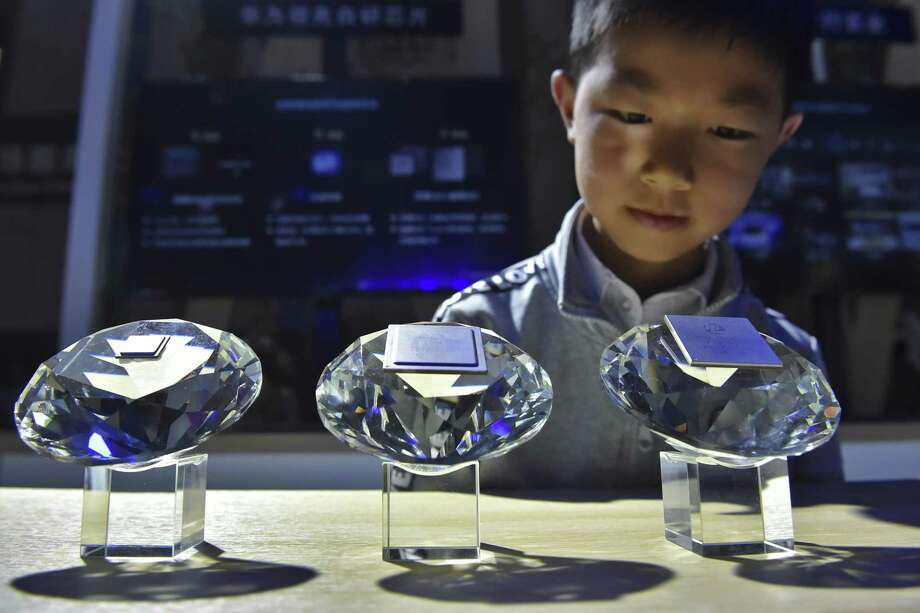 In this May 26 photo released by Xinhua News Agency, a child looks at the chips designed for 5G base stations on display at the China International Big Data Industry Expo 2019. Photo: Ou Dongqu / Associated Press / Xinhua