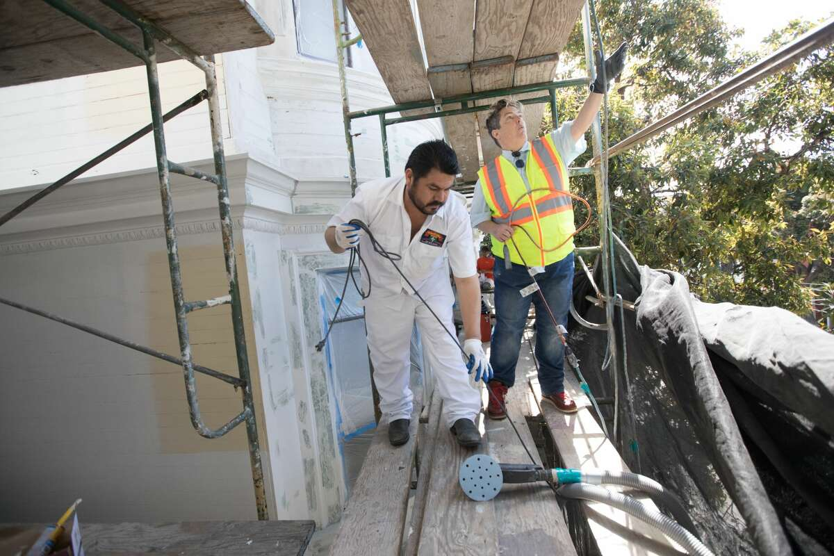 Nita Riccardi, right, helps Alberto Algo collect power cables to plug in a sander. She is supervising a repainting project being done on 450 Duboce Ave in San Francisco. Riccardi owns Winning Colors which specializes in rehabilitating and painting San Francisco's Victorian houses and buildings.