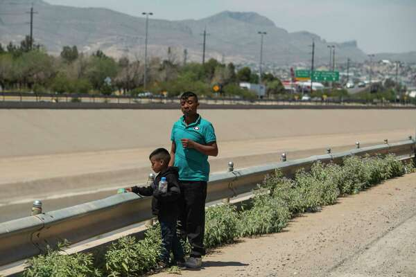 Lucas Pablo Perez and his father, Felipe Pablo Pedro, of Guatemala, wait to be picked up by Border Patrol agents in El Paso, Texas, on June 13, 2019, after crossing the Mexico border.