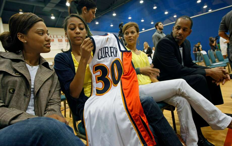 Golden State Warriors top draft pick Stephen Curry has his jersey passed between his girl friend Ayesha Alexander, left, and his sister Sydel Curry as mother Sonya Curry and father Dell Curry who played 16 seasons in the NBA looks on at Warriors headquarters in Oakland, Calif, Friday, June 26, 2009. Photo: Lance Iversen / The Chronicle