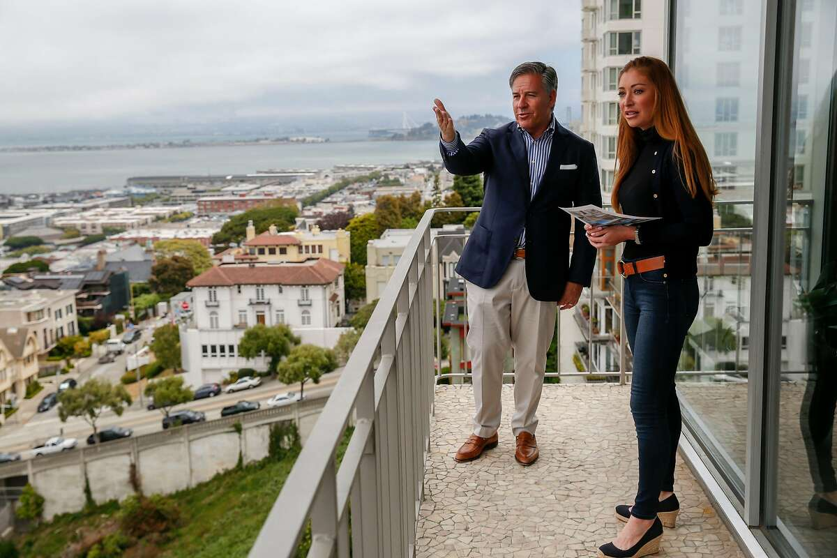 Realtor Gregg Lynn points out the view of the Golden Gate Bridge to Whitney Hudak as he shows her a condo at 1080 Chestnut in Russian Hill Wednesday, June 19, 2019, in San Francisco, Calif.