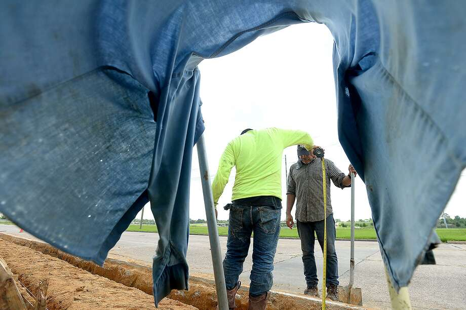 "Texas Concrete Co. co-workers Alex Rios (left) and Miguel Rocha wear protection from the sun and inhaling particles while putting in a sidewalk on Jim Gilligan Way Thursday. A heat advisory was issued for Southeast Texas Thursday, with ""feel like"" temperatures over 100 degrees. The high heat is expected to continue through Friday. People are advised to stay hydrated, wear protective head covering and avoid strenuous activity for prolonged periods of time. Photo taken Thursday, June 20, 2019 Kim Brent/The Enterprise Photo: Kim Brent / The Enterprise / BEN"