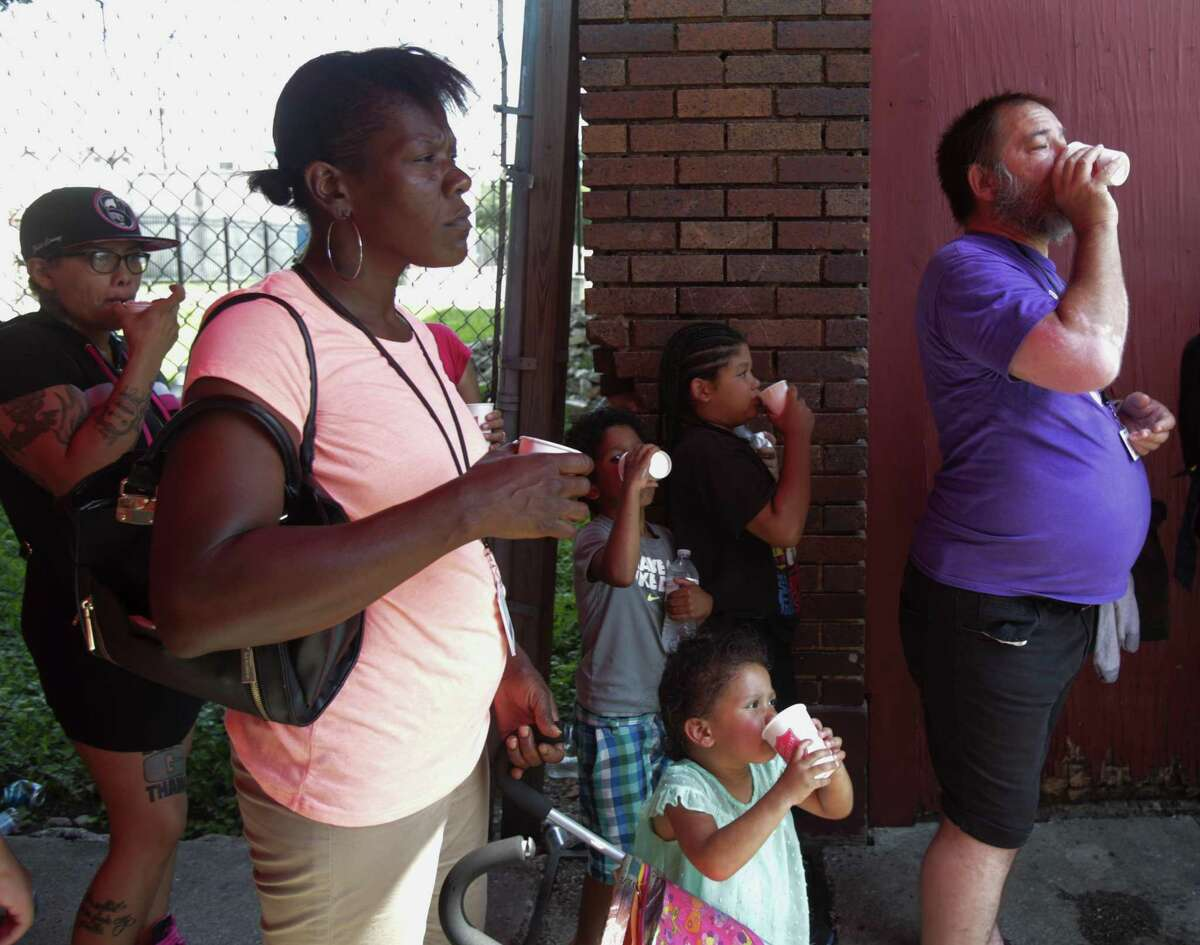 People line up to receive snow cones, water bottles, hygiene products and clothing handed out by members of the Salvation Army and Gonzaba Medical, at the intersection of North Frio and West Houston Streets. Thursday, June 20, 2019 in San Antonio. The weather has reached over 100 degrees this week according to the National Weather Service.