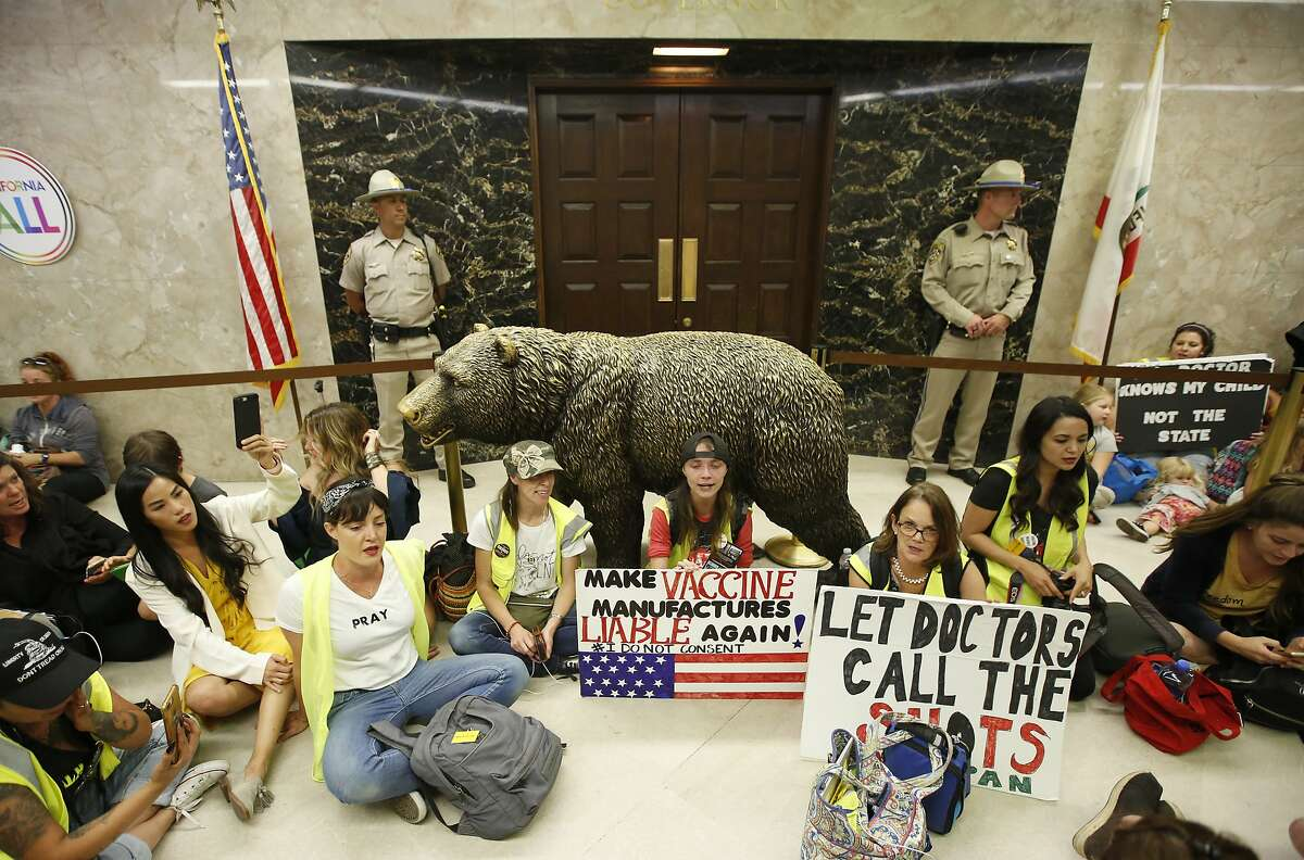 Opponents of a measure that would give public health officials oversight of doctors that may be giving fraudulent medical exemptions from vaccinations during gathered in front of the governor's office after it was approved by the Assembly Health Committee at the Capitol in Sacramento, Calif., Thursday, June 20, 2019.(AP Photo/Rich Pedroncelli)