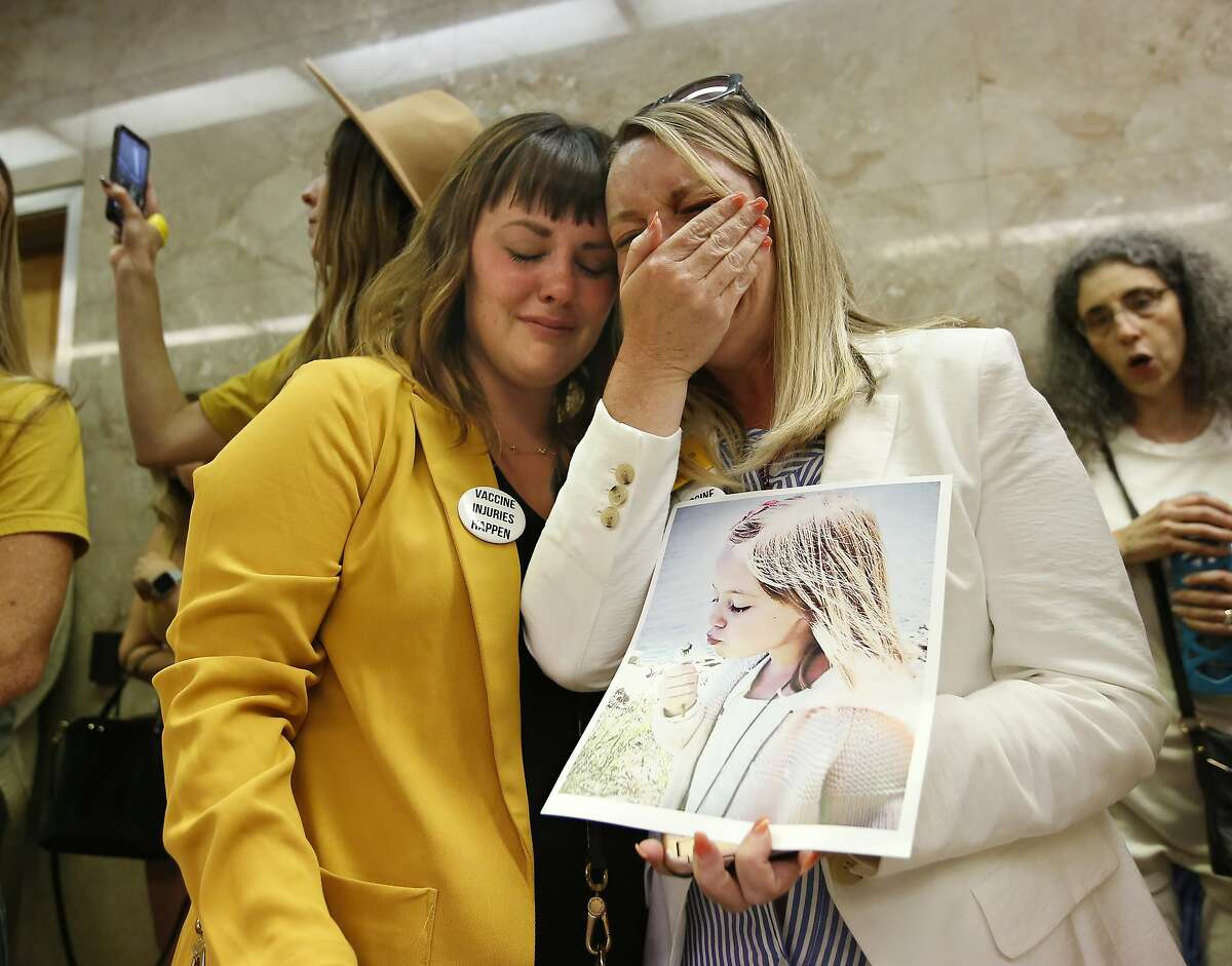 Jessica Purciful , left, and Angela Hicks, right, who both opposed a measure that would give public health officials oversight of doctors that may be giving fraudulent medical exemptions from vaccinations console each other after the bill SB276 was approved by the Assembly Health Committee at the Capitol in Sacramento, Calif., Thursday, June 20, 2019. (AP Photo/Rich Pedroncelli)