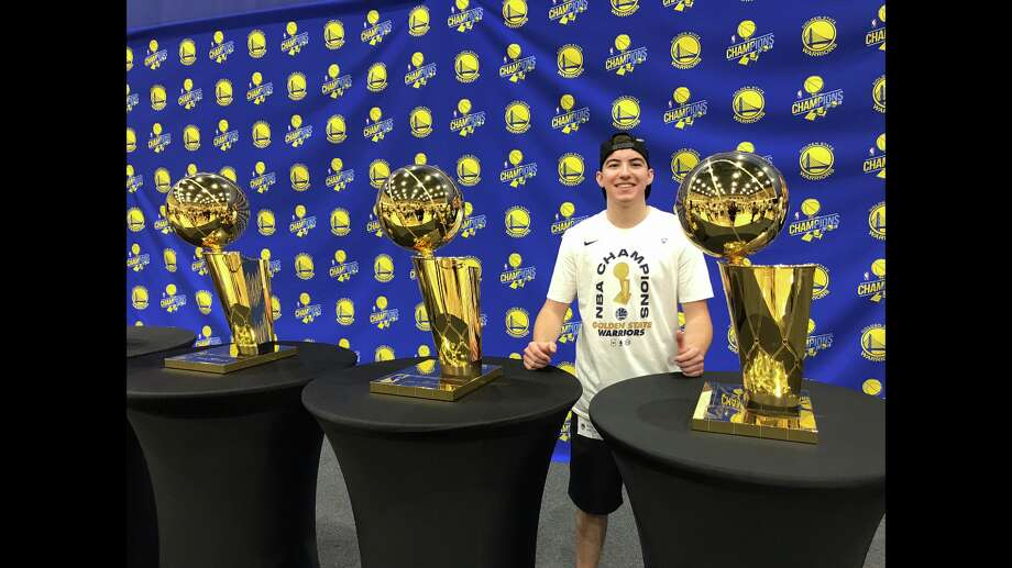 Golden State Warriors team attendant Anthony Silva poses for a photo with the Warriors' three most recently won Larry O'Brien Championship trophies. He's been working with the team as what's commonly known as a ball boy since 2018, but he does much more for the team than rebound and chase down basketballs. Here's what it's like to be a teenager working for one the world's most successful sports franchises. Photo: Photo Courtesy Of Amy Silva