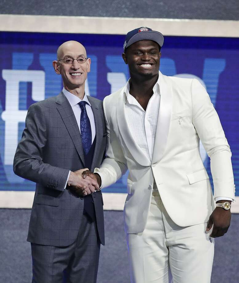 Zion Williamson (right) doesn't betray his emotions as the No. 1 pick poses with NBA Commissioner Adam Silver. Photo: Julio Cortez / Associated Press
