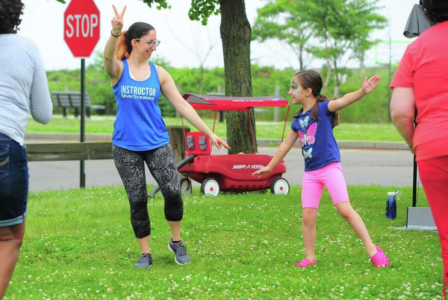 Thalia Matarese, 7, of Milford, moves along with her aunt, Lizz Petrakis as she leads a Silver Sneakers exercise session for seniors during the opening day of the Walnut Beach Farmers' Market at the Walnut Beach pavilion in Milford, Conn., on Thursday June 20, 2019. The market will be held every Thursday until Sept. 12 from 4-7 p.m. Photo: Christian Abraham / Hearst Connecticut Media / Connecticut Post
