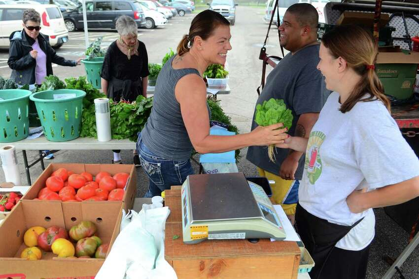 Karen Panza, of Stratford, buys vegetables from Rose Gazy, of Gazy Farms in Oxford during the opening day of the Walnut Beach Farmers' Market at the Walnut Beach pavilion in Milford, Conn., on Thursday June 20, 2019. The market will be held every Thursday until Sept. 12 from 4-7 p.m.