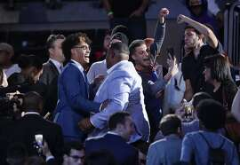 Michigan's Jordan Poole, left, celebrates after the Golden State Warriors selected him as the 28th pick overall in the NBA basketball draft Thursday, June 20, 2019, in New York. (AP Photo/Julio Cortez)