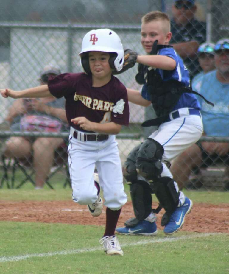 After finding his path to home plate blocked by Friendswood's catcher who has the ball, Deer Park Pinto 8U All-Star Aysen Miller turned around and headed for third base. He survived this pickle, scoring a tying run. He and his teammates are back this weekend, playing Saturday at 10 a.m. Photo: Robert Avery