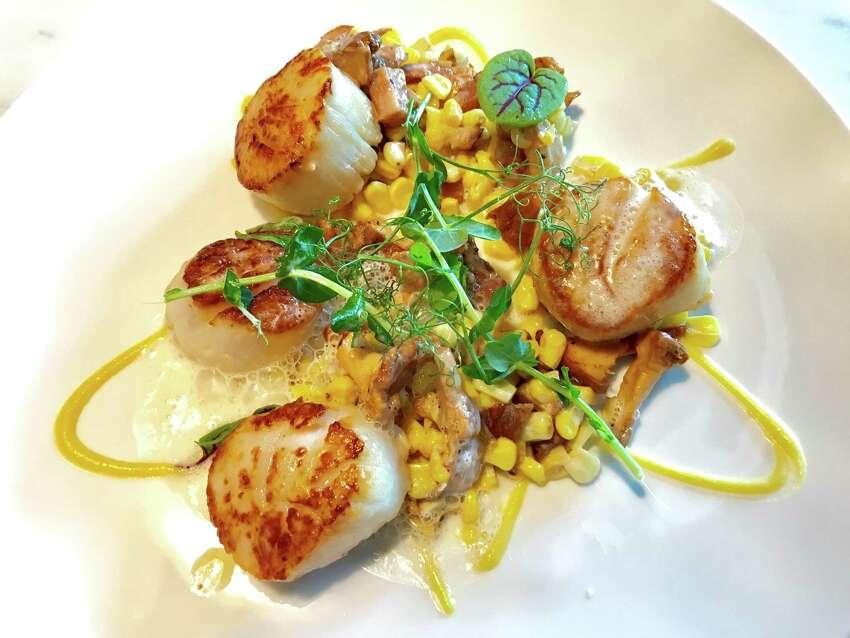 Maine diver scallops with pea puree, sauteed peas, corn, leeks and chanterelle mushrooms with bacon espuma.