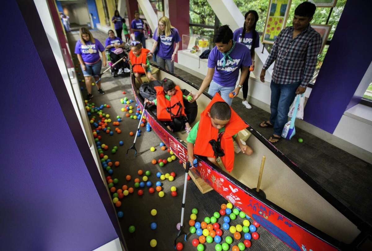 Neveah, from left, 4, Eshal, 5, and Jaiden, 7, pick up colorful balls from a canoe simulating a fishing trip from a hallway of the Texas Children's Hospital as part of a summer camp experience in the hospital on Tuesday, June 11, 2019, in Houston.