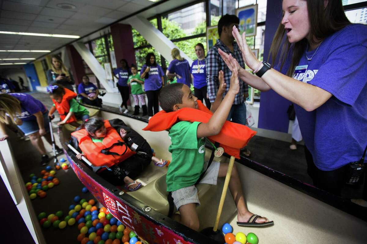 Jaiden, 7, high-fives a Camp For All staffer during a mock fishing trip in the hallway of the Texas Children's Hospital on Tuesday, June 11, 2019, in Houston.