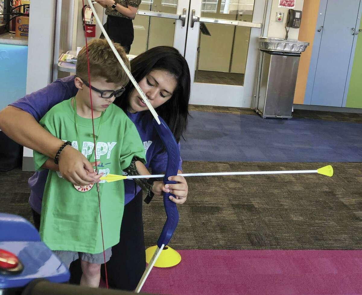 Jessi Amaro shows Collin, 6, how to use a bow and arrow during Camp For All 2U at Texas Children's main campus.
