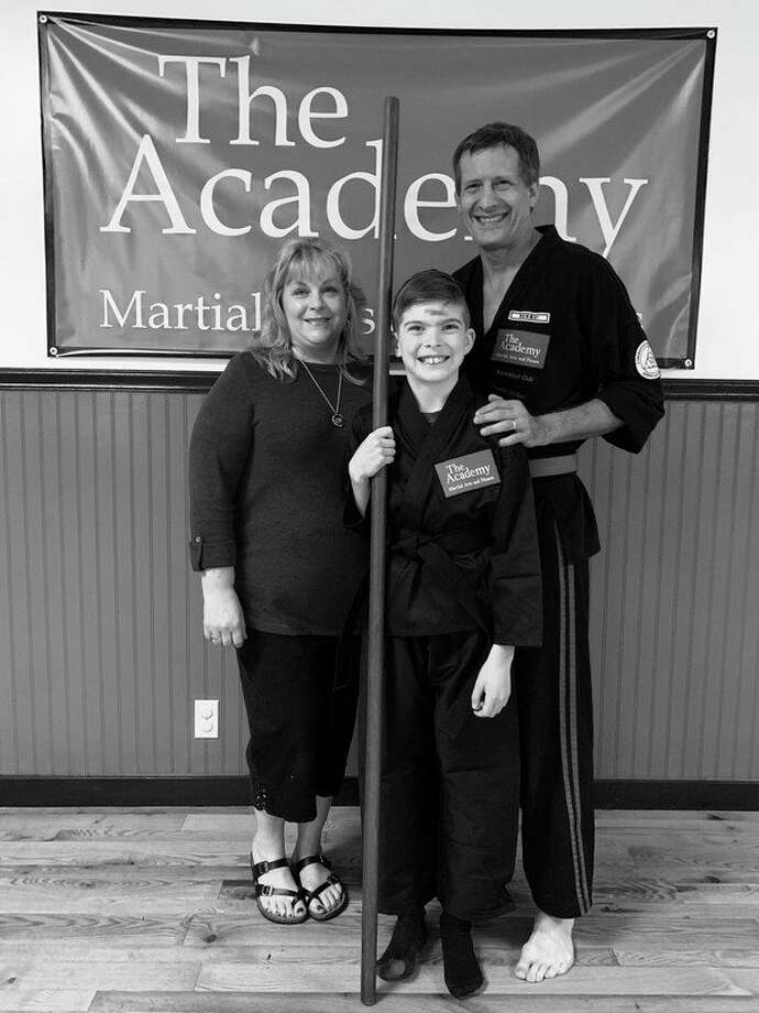 Ryan Stacy, center, recently earned The Academy Black Belt from The Academy Martial Arts and Fitness. 				At left is Laura Sira and at right is Craig Sira.