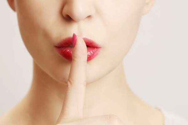 Woman holding her finger to her lips in a gesture for silence.